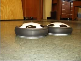 "Photo shows side view of two hover pucks"" on the floor."