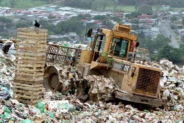 Photo shows a heavy piece of machinery driving over a landfill.