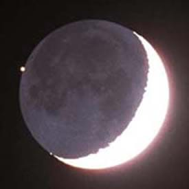 A photograph shows a gray round Moon in a black sky with one arc-ed edge of the moon (a crescent shape) glowing white and bright.