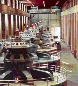 A row of seven gigantic cylindrical devices in a concrete room.