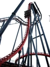 Photo shows a car coming down the first big hill of a roller coaster.