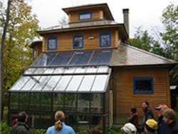 A photograph shows people standing outside a two-story house with one side looking like an attached greenhouse (lots of glass).