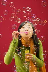 A girl blows through a bubble wand, creating a mass of floating soap bubbles.