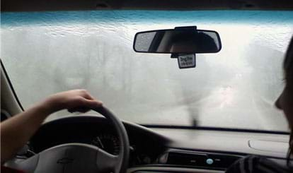Photo shows rain on windshield, obscuring the view of the road ahead.