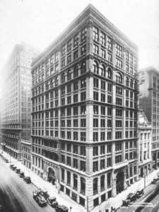 A black and white photograph shows a 14-story bilding on the corder of a city block.