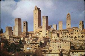 Photo of a town of stone buildings with tile roofs, including many tall towers that rise above the rest of the buildings.