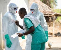 A photograph shows two healthcare workers fully gowned in white biohazard suits and blue gloves standing near a thatched-roof home as a third person writes one worker's name and time on the outside of his/her suit.