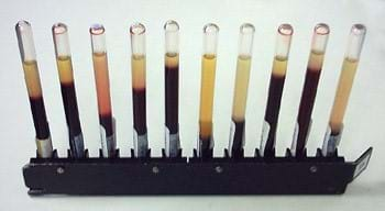 A photograph shows 10 round-style glass tubes lined up in a rack. Each tube with murky liquids inside shows a different sedimentation rate. The fifth tube from the left is the disease-free normal blood. The ESR value deviates from the normal value if a disease is present.