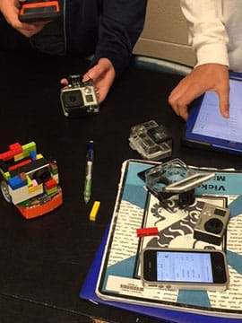 A photograph shows two students setting up a small (Edison) robot and handling a computer tablet, smartphone and digital camera. LEGO bricks on the robot are positioned to hold the camera.