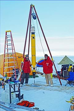 A photograph shows a snowy landscape in Antarctica with two people in red parkas standing on snow-covered ice near a long, cylindrical yellow device hanging from a triangular metal frame above a hole in the ice. They are preparing to deploy the Icefin robot through the hole into the water under the ice.