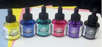 A photograph shows six small glass bottles Dr. Ph Martin's Bombay India ink: yellow, blue, green, red, purple, black. Each bottle has a black squeezable eye dropper as part of its screw-on cap, which can be used to distribute ink drops. Also shown is an assortment of light colored, inexpensive sheets of construction paper (pink, yellow, light blue, white).