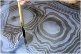 A photograph shows a bamboo paintbrush delicately poised above a shallow pool of water. On the surface of the water is a beautiful, rippling pattern of black ink concentric rings.
