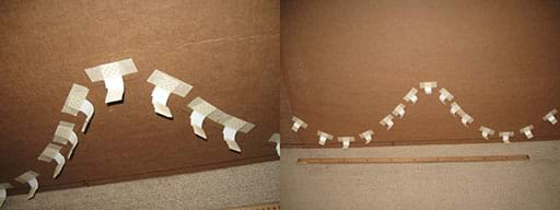 A wide composite photograph shows a horizontal cardboard backing being prepared for the roller coaster rail by the placement of 20 or more one-inch vinyl corner bead pieces taped to the cardboard along the hills and valleys of the roller coaster path. They serve as L-bracket supports for the pipe insulation rail, which is added next.