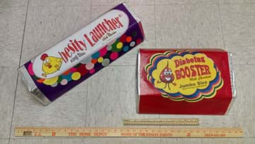 Two large candy bars lay on the floor next to a Home Depot yardstick and a ruler.