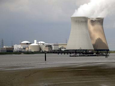 A photograph shows steam coming out of the tops of two Doel Nuclear Power Station cooling towers in Belgium.
