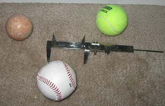 A photograph shows a marble sphere, tennis ball and baseball, plus a vernier caliper, which is a linear measuring instrument consisting of a scaled rule with a projecting arm at one end to which is attached a sliding vernier scale with a projecting arm that forms a jaw with the other projecting arm.