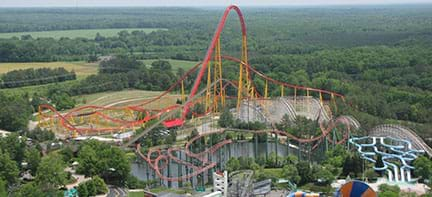 A wide photograph shows an aerial view of the entire Intimidator 305 roller coaster at Kings Dominion theme park, VA. The track route includes curves and loops over land and water with one very high climb and drop in the center of it all.