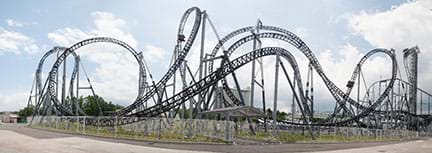 A wide photograph shows the Takabisha roller coaster in the Fuji-Q Highland theme park, Fujiyoshida, Yamanashi, Japan, which is famous for being the steepest coaster in the world with its 121° drop angle and for its $26 million cost. The photo shows a complicated, multiple curving and looping roller coaster rail structure.