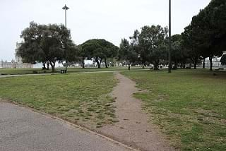 A dirt path crosses a green park between two established paved paths.