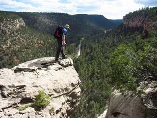 A person in hiking gear stands at the edge of a cliff overlooking a canyon.