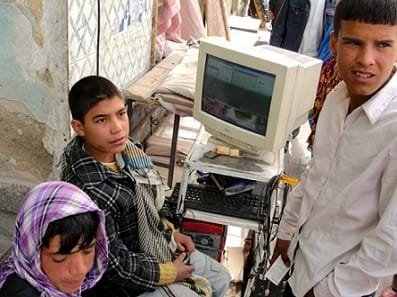 A photograph shows three children near a desktop computer with an older-style box-shaped monitor at an outdoor marketplace in Kabul, Afghanistan.