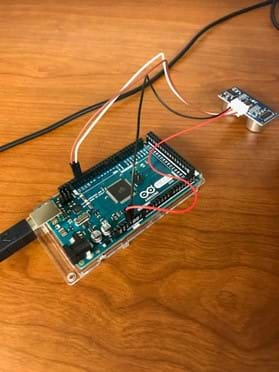 The image shows a breadboard with a USB cord connected to it.  Connected to the digital pins of the breadboard are the echo and trigger wires that connect to an ultrasound distance sensor.  The power and ground wires are connected on the opposite side near the analog pins.