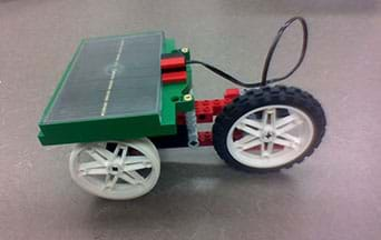 A photograph shows an example three-wheeled solar vehicle built with an eLAB LEGO Renewable Energy Set. A black solar panel is mounted on top, above the axle between two wheels.