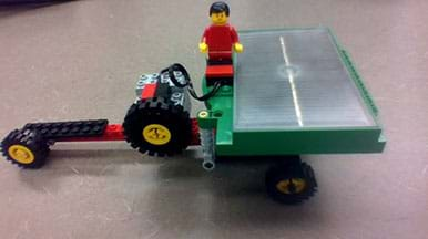 A photograph shows a small-size solar-powered wheeled vehicle made from an eLAB LEGO Renewable Energy Set. It has a long nose with a small wheel at the end and multiple wheels at the back, on which the solar panel is positioned. A LEGO person rides in the middle of the vehicle.