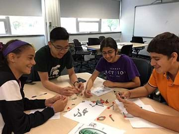 A photograph shows a group of students gathered around a classroom table and using a molecular model set to model the photosynthesis reaction.