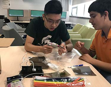 A photograph shows two teens at a classroom table constructing their prototype sunglasses. One student uses a hot glue gun to affix the polarizing filter while the other is assisting.