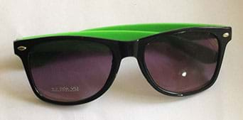 A photograph shows a pair of dark sunglasses with black and green frames.