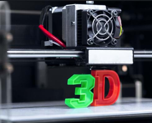 "A photo of a 3D printer head tool with two printed plastic examples below; a green ""3"" and a red ""D""."