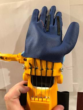 A blue rubber glove with black sensors on the back that have wires out of either end. The glove is on a 3D printed prosthetic hand with the fingers extended.