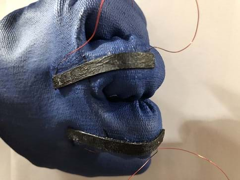 A blue rubber glove with black sensors on the back that have wires out of either end. The hand inside the glove is clenched in a fist.