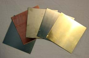 A photograph shows five squares of thin metal alloy materials of various metallic colors: grays, bronze, silver and gold.
