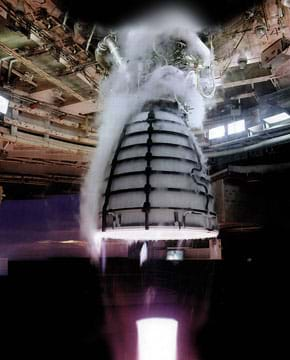A photograph shows an engine undergoing a hot-fire test. The engine looks like a half of a 3D ellipse covered in a grid-like casing and attached at its top to a structure designed for testing. Surrounding and above the engine is a cloud-like substance, which is the condensation produced from the propellant.