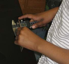 A photograph shows a student's hands as he uses digital calipers to measure the depth of his assigned alloy.
