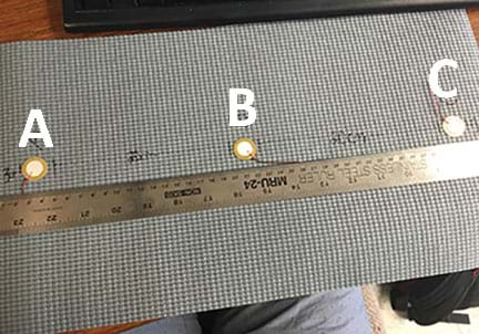 A photograph shows a gray rubber mat with three piezoelectric transducers (each looks like a small white circle with an attached wire) attached in a line and labeled A, B and C. Transducers A and C are located 3 cm from opposite mat edges with B located between them. All three are located 20 cm from each other. A ruler on the mat shows the distances.