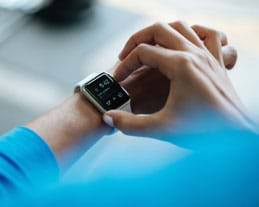 A photograph shows the right hands of a person pushing buttons a smart watch on her left wrist.