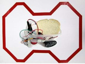 A composite photograph shows a continuous loop of red reflective tape on a 24 x 36-inch piece of white poster board. The route is a series of straight sections with periodic left and right turns, none greater than 45°. In the center is a Lunch-Bot carrying a slice of white bread. The Lunch-Bot is composed of a clear plastic food container with two drive servomotors with wheels taped to the bottom of one end of the container, a small cup taped to the bottom of the other end of the container (a support leg), sensors fastened to the front, a small breadboard taped to the outside front of the container, an Arduino microcontroller mounted inside front, and various wires that connect the servos, IR sensors and battery to the Arduino.