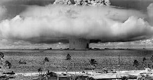 A black and white photograph from an island shows a mushroom-shaped explosion above the water at sea on the far horizon. This shows a nuclear weapon test by the U.S. military at Bikini Atoll, Micronesia, on July 25, 1946.