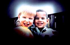 A photograph shows two smiling boys standing side-by-side, each holding a ball. The edges of the image are black, permitting only the center of the scene to be seen.