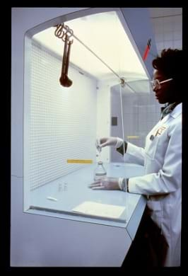 A photograph shows a lab tech in a white coat and gloves measuring liquid chemicals in a laboratory hooded area.