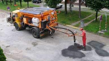 A photograph shows a road worker standing behind a truck in the middle of a street, using material flowing from a hose from the truck to patch potholes.