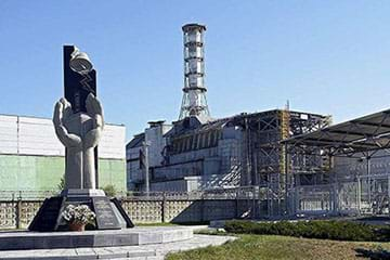 A photograph shows a monument shaped like a cupped pair of hands in front of the building remains of a power plant.