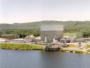 A photograph shows nuclear power plant, which looks like a compound of assorted short and tall buildings along the bank of a river.