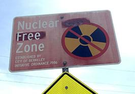A photograph shows a metal roadway sign that says: Nuclear Free Zone. Established by City of Berkeley initiative ordinance 1986.