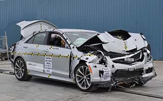 A photograph shows a silver sedan after a vehicle crash test, with a good view of the front and passenger sides of the vehicle. The hood, bumper, grill and engine are smashed and crumpled. The front passenger air bag and window air bag have been deployed. The trunk is open.