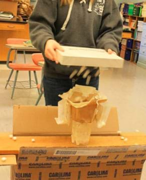 A photograph shows a student holding a flat rectangular-shaped box over a student-designed transport protein model with mini marshmallows coming out of the box.