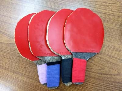 Four biocomposite ping-pong paddle prototypes lay on a table.